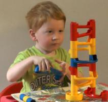 Toddler sitting erect on a chair building a marble run.